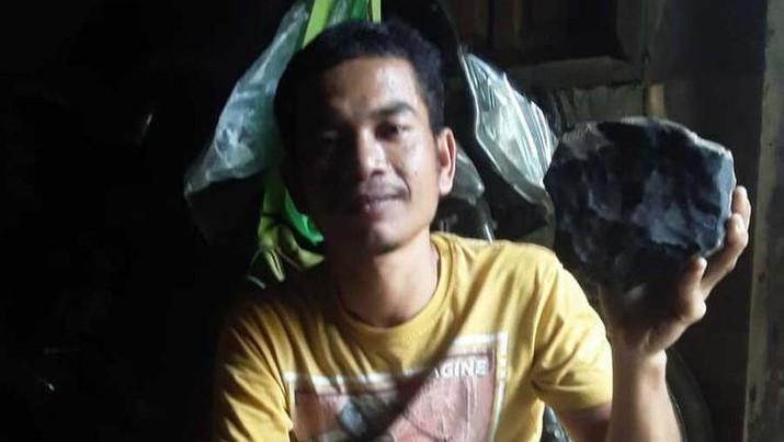 Josua Hutagalung (33) warga Dusun Sitahan Barat, Desa Satahi Nauli, Kecamatan Kolang, Kabupaten Tapanuli Tengah menunjukkan batu yang diduganya sebagai meteor setelah jatuh menimpa rumahnya, Sabtu (1/8/2020).(handout)