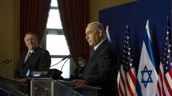 Menteri Luar Negeri AS Mike Pompeo, kiri, mendengarkan Perdana Menteri Israel Benjamin Netanyahu berbicara selama pernyataan bersama mereka setelah pertemuan di Yerusalem, Kamis, (19/11/2020). (AP/Maya Alleruzzo)
