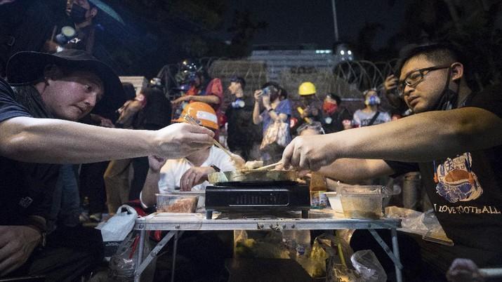 Para pengunjuk rasa membuat hotpot di depan markas polisi saat rapat umum di Bangkok, Thailand. (AP/Wason Wanichakorn)