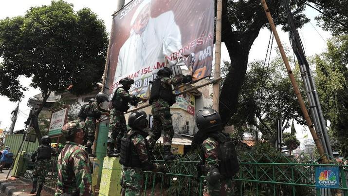 Sejumlah Anggota TNI mencopot baliho bergambar wajah pimpinan Front Pembela Islam (FPI) Habib Rizieq Syihab di Kawasan Tn Abang, Jakarta, Jumat 20/11/2020). (CNBC Indonesia/Muhammad Sabki)