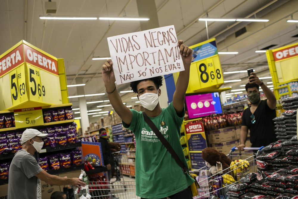 Activists including members of Black Lives Matter demonstrate inside a Carrefour supermarket against the murder of Black man Joao Alberto Silveira Freitas at a different Carrefour the night before, on Brazil's National Black Consciousness Day in Rio de Janeiro, Brazil, Friday, Nov. 20, 2020. Freitas died after being beaten by supermarket security guards in the southern Brazilian city of Porto Alegre, sparking outrage as videos of the incident circulated on social media. (AP Photo/Bruna Prado)