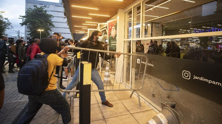 Demonstrators use a crowd control barrier to smash into the entrance of a Carrefour supermarket during a protest against the murder of Black man Joao Alberto Silveira Freitas at a different Carrefour supermarket the night before, on Brazil's National Black Consciousness Day in Rio de Janeiro, Brazil, Friday, Nov. 20, 2020. Freitas died after being beaten by supermarket security guards in the southern Brazilian city of Porto Alegre, sparking outrage as videos of the incident circulated on social media.  (AP Photo/Andre Penner)