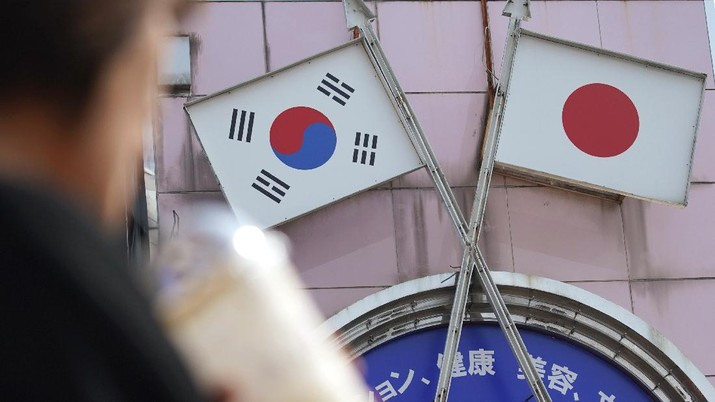 FILE - In this Aug. 2, 2019, file photo, a woman walks past an advertisement featuring Japanese and South Korean flags at a shop in Shin Okubo area in Tokyo. The leaders of China, Japan and South Korea are holding their latest trilateral summit in China this week, amid feuds over trade, military maneuverings and historical animosities. Most striking has been a complex dispute between Seoul and Tokyo, while Beijing has recently sought to tone-down its disagreements with its two neighbors.(AP Photo/Eugene Hoshiko, File)