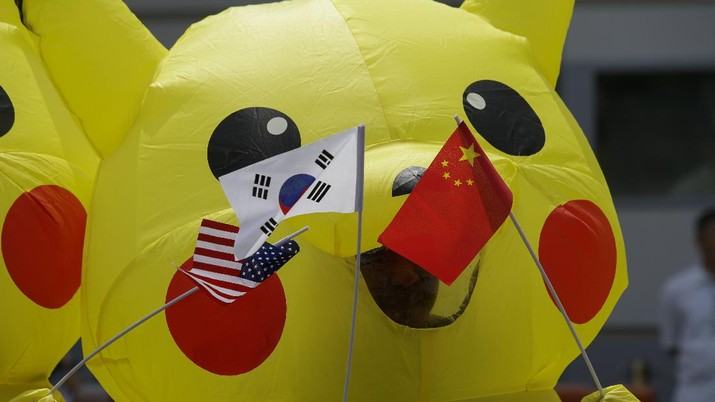 Environmental activists wearing Pikachu costumes hold flags of U.S., Japan and China during a rally in front of the Japanese embassy in Manila, Philippines on Tuesday, June 25, 2019. The group is challenging Japan to stop financing coal as it prepares to host the Group of 20 leaders summit. (AP Photo/Aaron Favila)