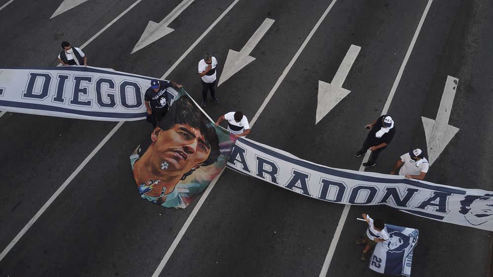 Soccer fans carry a banner of Diego Maradona in downtown Buenos Aires, Argentina, Wednesday, Nov. 25, 2020. Diego Maradona, the Argentine soccer great who was among the best players ever and who led his country to the 1986 World Cup title died from a heart attack at his home in Buenos Aires. He was 60. (AP Photo/Victor Caivano)