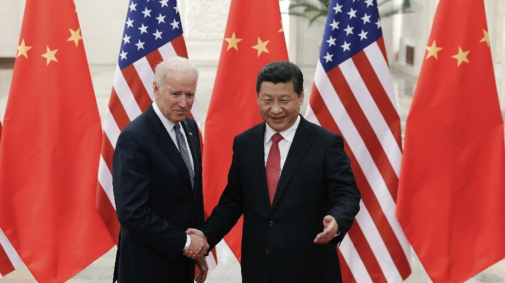 FILE - In this Dec. 4, 2013, file photo, Chinese President Xi Jinping, right, shakes hands with then U.S. Vice President Joe Biden as they pose for photos at the Great Hall of the People in Beijing. As Americans celebrate or fume over the new president-elect, many in Asia are waking up to the reality of a Joe Biden administration with decidedly mixed feelings. Relief and hopes of economic and environmental revival jostle with needling anxiety and fears of inattention. The two nations are inexorably entwined, economically and politically, even as the U.S. military presence in the Pacific chafes against China's expanded effort to have its way in what it sees as its natural sphere of influence. (AP Photo/Lintao Zhang, Pool, File)