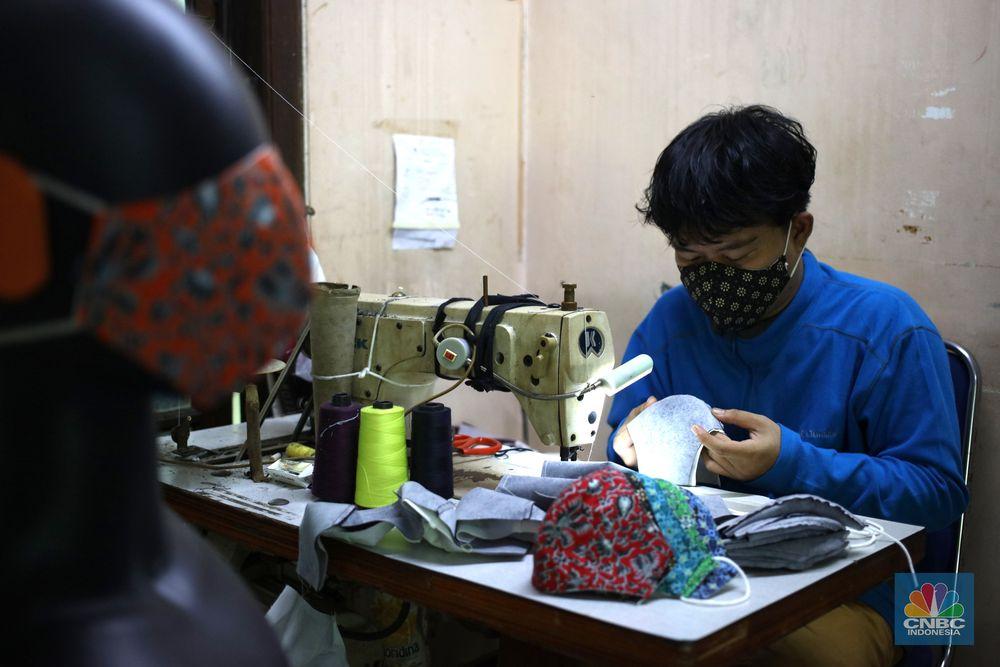 Pekerja menyelesaikan pembuatan masker kain di rumah produksi K-A-in (Kreasi Anak Indonesia) di Petukangan Utara, Jakarta Selatan, Kamis (26/11/2020). Dalam sehari rumah produksi ini mampu menghasilkan 1200 pcs masker kain. (CNBC Indonesia/Tri Susilo)   Samsul (46) sudah merintis usaha sejak tahun 2000 menekuni rumah produksi yang dinantu dengan puluhan pekerja otorsing.   Pandemi Covid-19 membuat Samsul kebanjiran order dari berbagai instansi maupun diluar instansi.   Sebut saja seperti pembuatan masker KPK, TNI POLRI, POLDA Sumsel hingga sekolah dibeberapa daerah tim rumah produksi yang mengerjakannya.   Samsul mengatakan