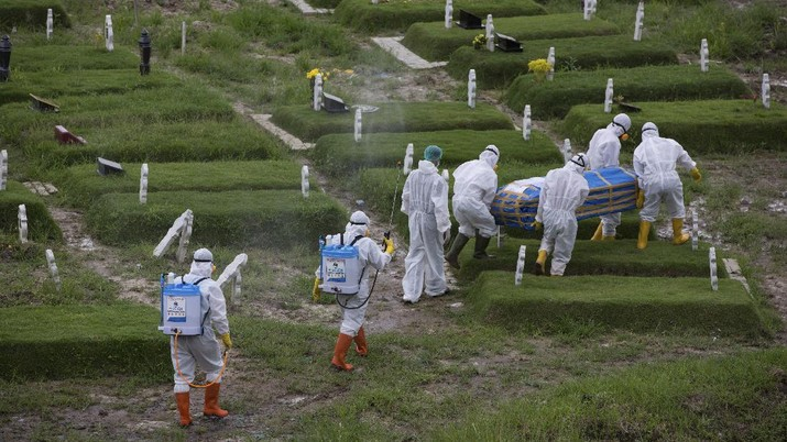 Workers in protective suits carry a coffin containing the body of someone who presumably died of the coronavirus for burial in Medan, North Sumatra, Indonesia, Tuesday, Nov. 24, 2020.(AP Photo/Binsar Bakkara)