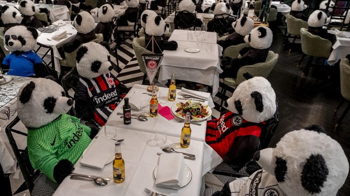 Plush pandas and Corona beer bottles decorate the tables of a closed restaurant in Frankfurt, Germany, Tuesday, Nov. 24, 2020. Restaurants all over Germany were closed as a partial lockdown began in November to avoid the further outspread of the coronavirus. (AP Photo/Michael Probst)