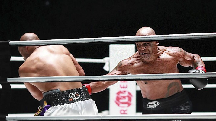 In a photo provided by Triller, Mike Tyson throws a punch during the fourth round against Roy Jones Jr. in an exhibition boxing bout Saturday, Nov. 28, 2020, in Los Angeles. The bout was unofficially ruled a draw by the WBC judges at ringside. Tyson and Jones fought eight two-minute rounds, and both emerged smiling and apparently healthy from a highly unusual event. (Joe Scarnici/Triller via AP)