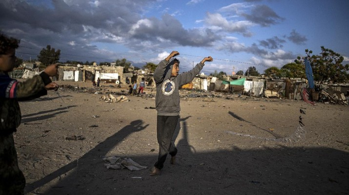 A Palestinian girl walks next to a donkey carte loaded with rocks in a slum on the outskirts of Khan Younis Refugee Camp, in the southern Gaza Strip, Wednesday, Nov. 25, 2020. Israel's blockade of the Hamas-ruled Gaza Strip has cost the seaside territory as much as $16.7 billion in economic losses and caused its poverty and unemployment rates to skyrocket, a U.N. report said Wednesday, as it called on Israel to lift the 13-year closure. (AP Photo/Khalil Hamra)