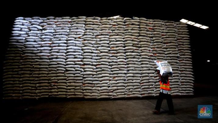 Pekerja mengangkut beras milik Perum Bulog di kawasan Kelapa gading, Jakarta, Senin (30/11/2020). Kementan kembali memastikan meski tengah dilanda pandemi Covid-19 pasokan beras hingga akhir tahun masih ada stok sebanyak 1,05 juta ton. (CNBC Indonesia/Tri Susilo)