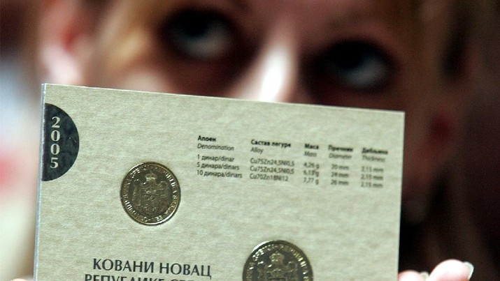 A National Bank employee displaying new coins of the national currency dinar, with a traditional Serbian coat of arms which was abolished during decades of Communist rule, in Belgrade, Friday, July 1, 2005. Serbia is part of Serbia-Montenegro union but the two republics use different currencies and have separate monetary system. (AP Photo/Darko Vojinovic)