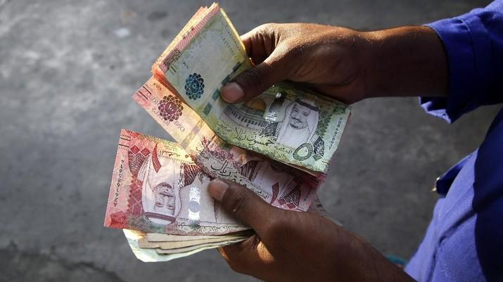 A station attendant counts Saudi Riyal cash as he waits for customers at a gas station in Jiddah, Saudi Arabia, Wednesday, Nov. 13, 2019. (AP Photo/Amr Nabil)