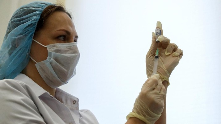 A Russian medical worker prepares a shot of Russia's Sputnik V coronavirus vaccine in Moscow, Russia, Saturday, Dec. 5, 2020. Thousands of doctors, teachers and others in high-risk groups have signed up for COVID-19 vaccinations in Moscow starting Saturday, a precursor to a sweeping Russia-wide immunization effort. (AP Photo/Pavel Golovkin)