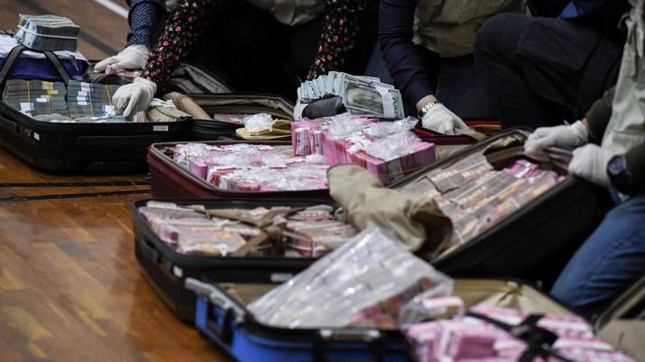 Penyidik KPK menunjukan barang bukti uang tunai saat konferensi pers terkait Operasi Tangkap Tangan (OTT) tindak pidana korupsi pada program bantuan sosial di Kementerian Sosial untuk penanganan Covid-19 di Gedung KPK, Jakarta, Minggu (6/12/2020) dini hari. (Dok: Humas KPK)