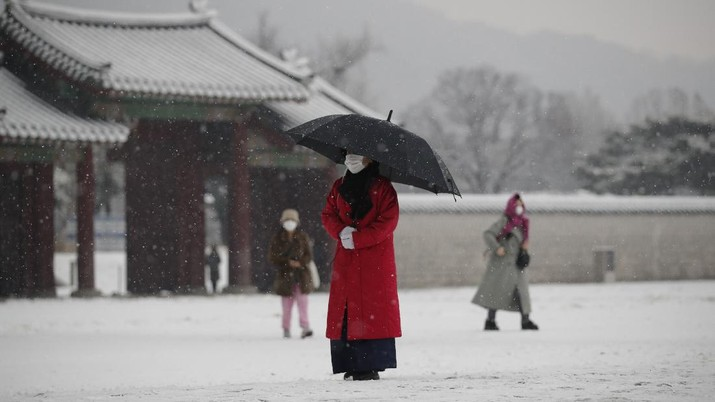 An employee wearing a face mask as a precaution against the coronavirus uses an umbrella to take shelter from the snow at the Gyeongbok Palace, one of South Korea's well-known landmarks, in Seoul, South Korea, Sunday, Dec. 13, 2020. (AP Photo/Lee Jin-man)