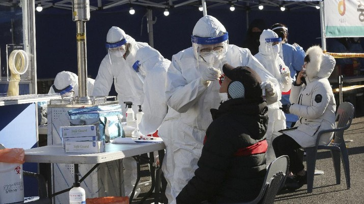 A medical worker takes samples from a man during a COVID-19 testing at a makeshift clinic in Seoul, South Korea, Monday, Dec. 14, 2020. South Korea was opening dozens of free COVID-19 testing sites in the greater Seoul area, as the country registered additional more than 700 new cases Monday amid a surge in infections. (AP Photo/Ahn Young-joon)
