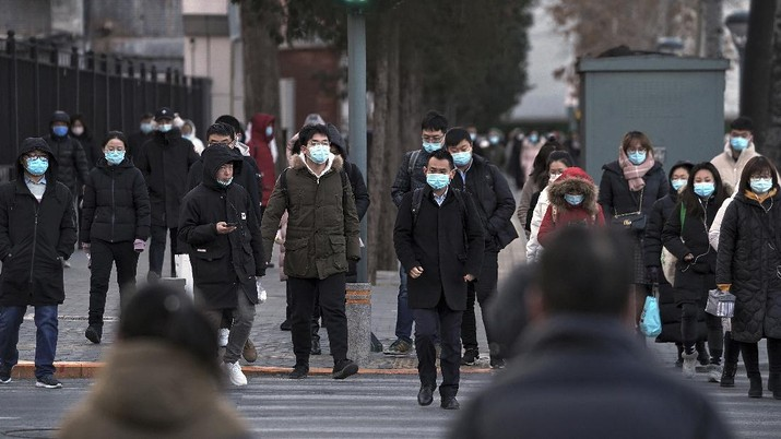 People wearing face masks to help curb the spread of the coronavirus walk across a street as they head for work during the morning rush hour in Beijing, Tuesday, Dec. 15, 2020. (AP Photo/Andy Wong)