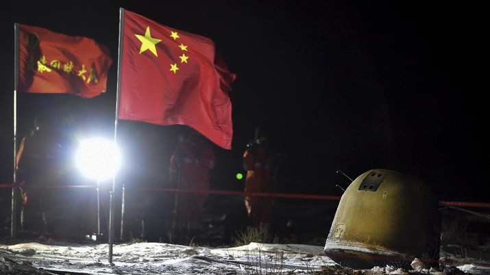 In this photo released by Xinhua News Agency, recovery crew members film the capsule of the Chang'e 5 probe after its successful landed in Siziwang district, north China's Inner Mongolia Autonomous Region on Thursday, Dec. 17, 2020. A Chinese lunar capsule returned to Earth on Thursday with the first fresh samples of rock and debris from the moon in more than 40 years. (Ren Junchuan/Xinhua via AP)