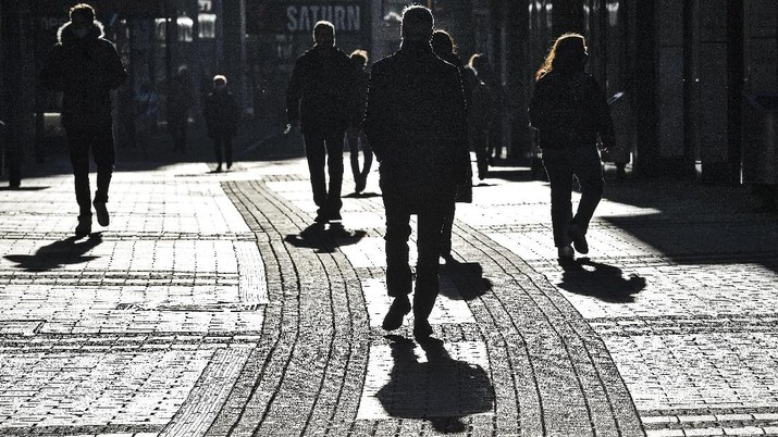 People walk the main shopping street in Cologne Germany, Wednesday, Dec. 16, 2020. Germany has entered a harder lockdown, closing shops and schools in an effort to bring down stubbornly high new cases of the coronavirus. (AP Photo/Martin Meissner)