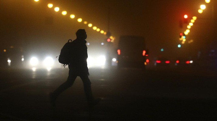 A man wears a face mask as he crosses a road early morning in Munich, Germany, Wednesday, Dec. 16, 2020. Germany has entered a harder lockdown, closing shops and schools in an effort to bring down stubbornly high new cases of the coronavirus. (AP Photo/Matthias Schrader)