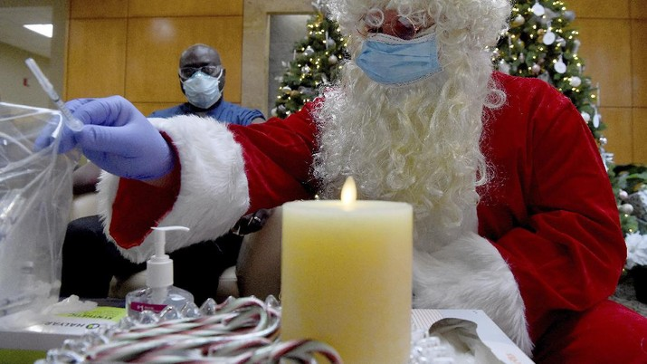 Santa, Robert Carroll, M.D., an Emergency Medicine Specialist with Manchester Memorial Hospital, takes a syringe from the plastic bag with already prepared dosages of the Pfizer-BioNTech vaccine, to be administered to Marvin Bristol, rear, a respiratory therapist and a front-line healthcare worker, Wednesday, Dec. 16, 2020, in Manchester, Conn. (Jim Michaud/Journal Inquirer via AP)
