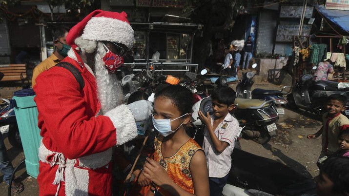 A man dressed as Santa Claus sanitizes an autorickshaw in Dharavi, one of Asia's biggest slums, in Mumbai, India, Saturday, Dec. 19, 2020. India's coronavirus cases have crossed 10 million with new infections dipping to their lowest levels in three months, as the country prepares for a massive COVID-19 vaccination in the new year. (AP Photo/Rafiq Maqbool)