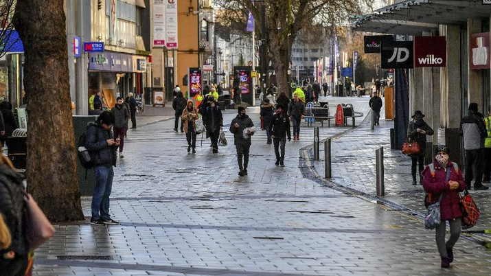 People walk through Cardiff city centre, Sunday Dec. 20, 2020. In Wales, authorities said they decided to move up a lockdown planned for after Christmas and people must stay at home from 12:01 a.m. Sunday. The move will largely scrap Christmas gatherings in line with the rules for southern England. (Ben Birchall/PA via AP)