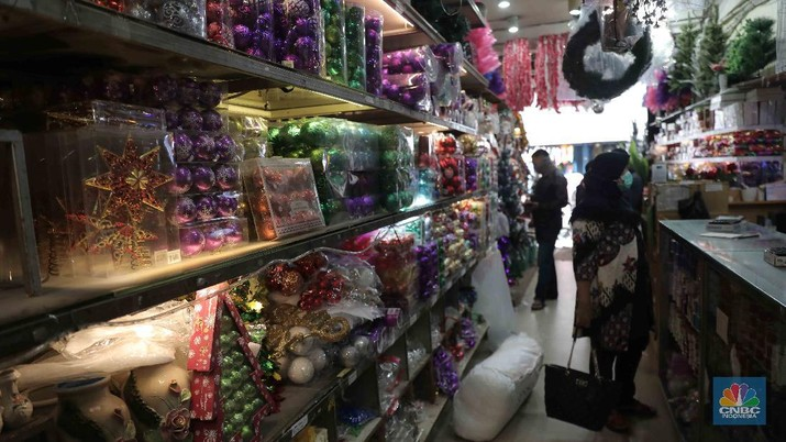 "Calon pembeli memilih hiasan Natal di Pasar Asemka, Jakarta, Selasa, 22 Desember 2020. Berbagai pernak-pernik Natal untuk hiasan pohon dan rumah dijual berkisar dari harga Rp 5 ribu hingga Rp 2 juta, kebanyakan berasal dari Tiongkok. Pasar Asemka, Jakarta Barat dapat menjadi rekomendasi bagi warga yang ingin menghiasi rumah dengan cantik namun dengan harga yang terjangkau. Terlebih, semua pernak-pernik natal sedang diskon. ""Iya kami lagi diskon itu saja hiasan natal yang bulat-bulat satu pack isi 3 bola tadinya Rp 60 ribu kita diskon jadi Rp 35 ribu,"" kata salah satu penjual, Menariknya, untuk pohon natal sendiri yang berukuran kecil (1 meter) pedagang memasang harga dari Rp 350 ribu hingga Rp 400 ribu. Lalu, pilihan warna pohon pun beragam di kawasan ini sehingga pembeli memiliki banyak pilihan. (CNBC Indonesia/ Muhammad Sabki)"