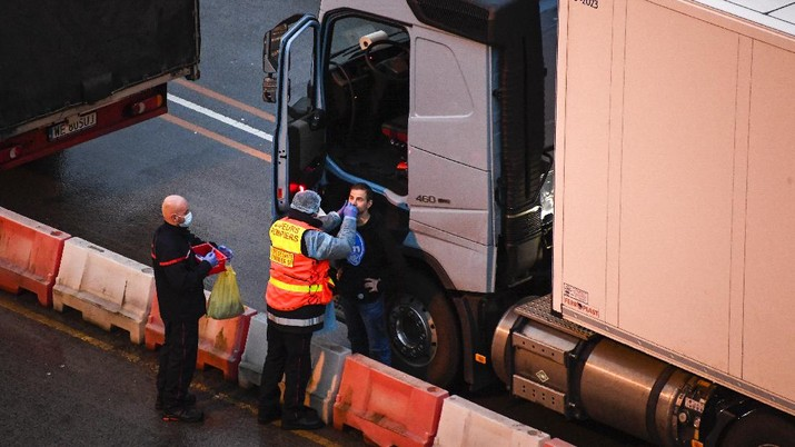 French officers make a COVID-19 test to a truck driver in the Port of Dover in Dover, England, Thursday, Dec. 24, 2020. Freight from Britain and passengers with a negative virus test have begun arriving on French shores, after France relaxed a two-day blockade over a new virus variant. The blockade had isolated Britain, stranded thousands of drivers and raised fears of shortages. (AP Photo/Alberto Pezzali)
