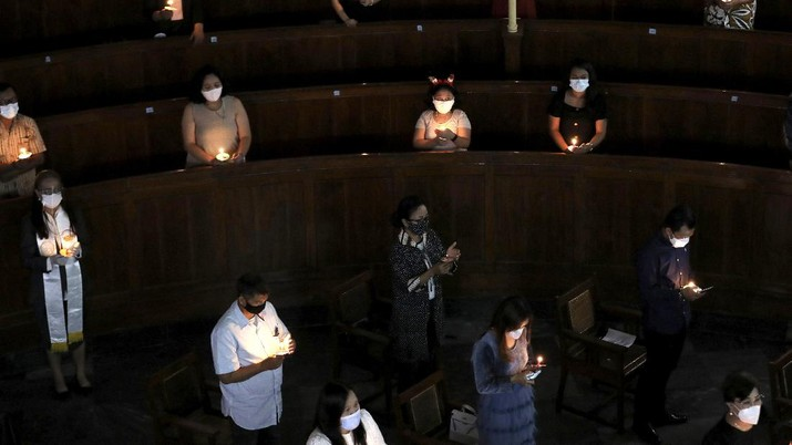 Worshippers sit spaced apart to prevent the spread of coronavirus outbreak as they light candles during a Christmas Eve service at Immanuel Church in Jakarta, Indonesia, Thursday, Dec. 24, 2020. Christmas celebrations in Indonesia will be a low-key affair amid surging coronavirus cases in the world's fourth most populous nation. (AP Photo/Dita Alangkara)