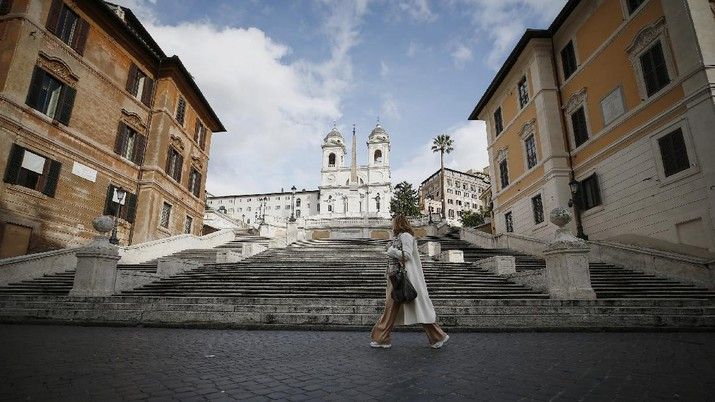 A woman walks past the Spanish Steps in Rome, Thursday, Dec. 24, 2020. Italy went into a modified nationwide lockdown Thursday for the Christmas and New Year period, with restrictions on personal movement and commercial activity similar to the 10 weeks of hard lockdown Italy imposed from March to May when the country became the epicenter of the outbreak in Europe. (Cecilia Fabiano/LaPresse via AP)