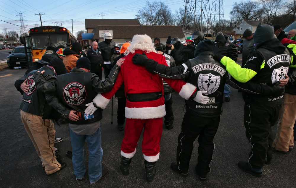 Santa Claus completes the circle with faith-based motorcycle riders and others as they pray before their 3rd Annual Reindeer Ride outside Mann Meats in Florissant, Mo., Friday, Dec. 24, 2020. Santa, in other seasons known as T.J. Harris of the Faithful Few motorcycle club, he joined a procession to deliver gifts to a girl battling neuroblastoma in St. Peters. (Robert Cohen/St. Louis Post-Dispatch via AP)