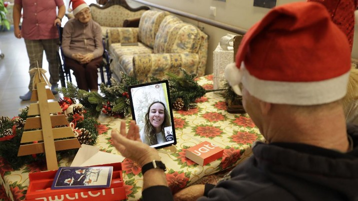 Roberto Capellini, is flanked by carer Michela Valle, right, and director Maria Giulia Madaschi, as he talks on  video call with Carolina Giannesi, a donor unrelated to her, who bought and sent her a Christmas present through an organization dubbed