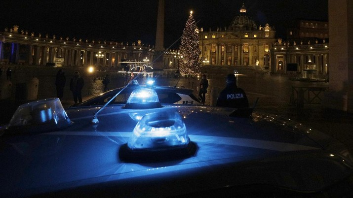 Police watch over as faithful pray outside St. Peter's Square, at the Vatican, Thursday, Dec. 24, 2020. Police in Italy are enforcing new COVID-19 travel restrictions aimed at limiting far-flung families from gathering over Christmas. Public health officials appealed for people to use common sense to prevent new infections over the holidays as a modified nationwide lockdown took effect Thursday. (AP Photo/Gregorio Borgia)