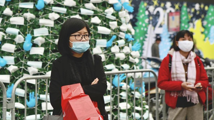 A masked security guard stands watch in front of a coronavirus-themed Christmas tree decorated with masks and rubber gloves in Hanoi, Vietnam, Thursday, Dec. 24, 2020. (AP Photo/Hau Dinh)