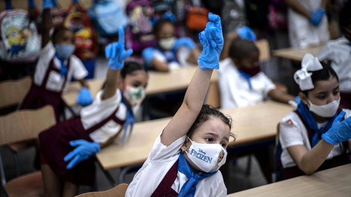 Foto terbaik AP 2020, Mengenakan masker dan sarung tangan plastik untuk mencegah penyebaran virus corona, anak perempuan mengangkat tangan saat di Havana, Kuba. (AP/Ramon Espinosa)