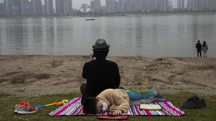 Foto terbaik AP 2020, Seorang anak yang mengenakan masker untuk melindungi diri dari virus korona berada di tepi Sungai Yangtze di Wuhan di provinsi Hubei China tengah pada. (AP/Ng Han Guan)