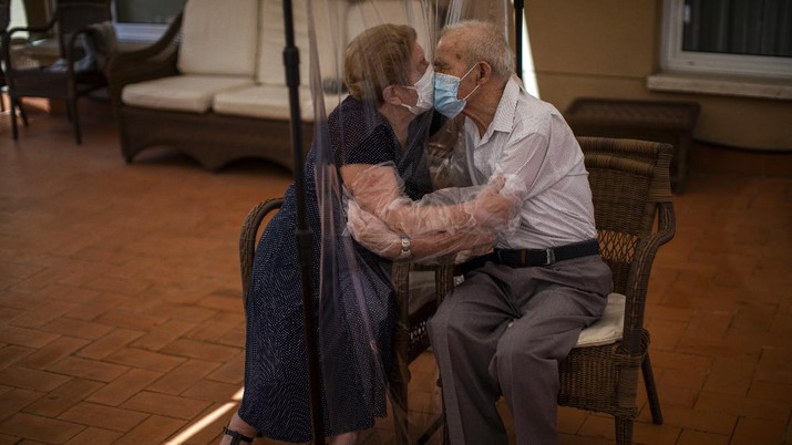 Agustina Cañamero (81) dan Pascual Pérez (84) berpelukan dan berciuman dengan dihalangi plastik untuk menghindari tertular virus corona di panti jompo di Barcelona, Spanyol, Senin, 22 Juni 2020. (AP / Emilio Morenatti)