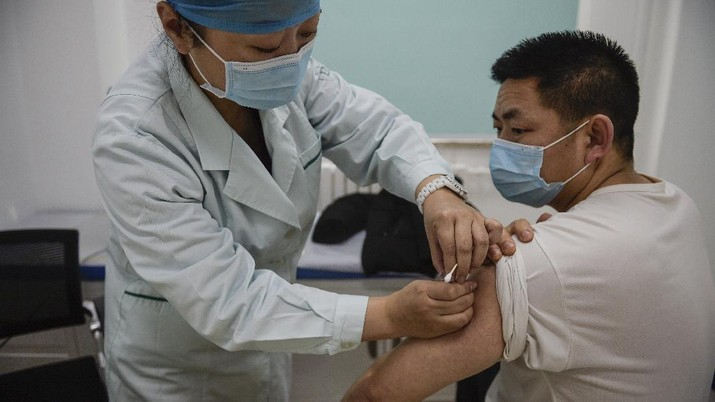 In this photo released by Xinhua News Agency, a medical worker injects a man with a COVID-19 vaccine at a healthcare center in Beijing, China, Saturday, Jan. 2, 2021. China authorized its first homegrown COVID-19 vaccine for general use on Dec. 31, 2020, adding another shot that could see wide use in poorer countries as the virus surges back around the globe. (Peng Ziyang/Xinhua via AP)
