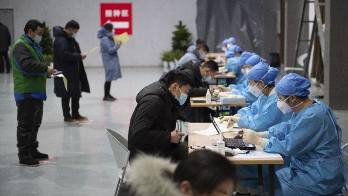 In this photo released by Xinhua News Agency, residents fill out content forms before receiving their COVID-19 vaccinations at a temporary vaccination site in Beijing, Saturday, Jan. 2, 2021. China authorized its first homegrown COVID-19 vaccine for general use on Dec. 31, 2020, adding another shot that could see wide use in poorer countries as the virus surges back around the globe. (Chen Zhonghao/Xinhua via AP)