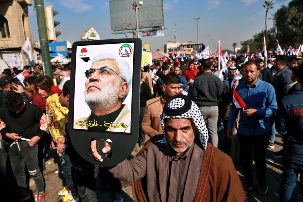 Supporters of the Popular Mobilization Forces hold a posters of Abu Mahdi al-Muhandis, deputy commander of the Popular Mobilization Forces, front, and General Qassem Soleimani, head of Iran's Quds force during a protest, in Tahrir Square, Iraq, Sunday, Jan. 3, 2021. Thousands of Iraqis converged on a landmark central square in Baghdad on Sunday to commemorate the anniversary of the killing of Soleimanil and al-Muhandis in a U.S. drone strike. (AP Photo/Khalid Moha