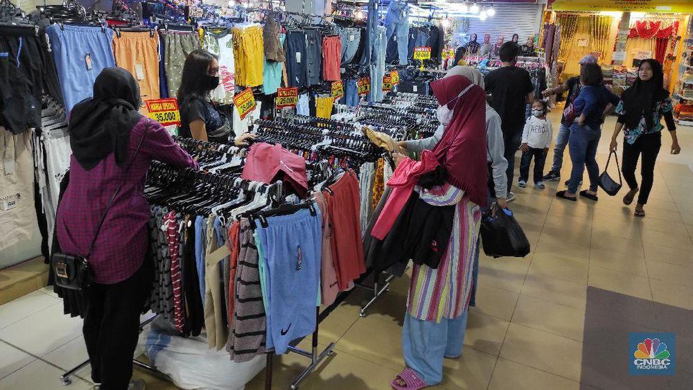 Pengunjung memlih pakaian yang dijual di salah satu pusat perbelanjaam di Kawasan Depok, Jawa Barat, Selasa (5/1/2021). Badan Pusat Statistik (BPS) memberi sinyal bahwa daya beli masyarakat mulai membaik karena salah satu indikatornya yakni inflasi komponen inti tumbuh positif mencapai 0,05 persen pada Desember 2020. (CNBC Indonesia/Andrean Kristianto)
