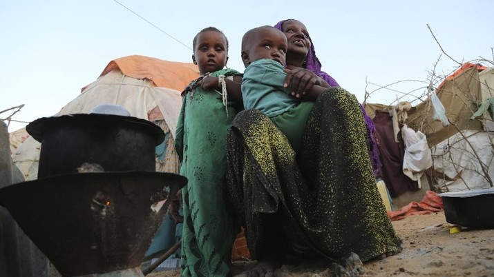 An internal displaced woman with her children cooks food near their makeshift shelter in Daynile camp in Mogadishu, Somalia on Thursday Dec. 17, 2020. As richer countries race to distribute COVID-19 vaccines, Somalia remains the rare place where much of the population hasn't taken the coronavirus seriously. Some fear that's proven to be deadlier than anyone knows. (AP Photo/Farah Abdi Warsameh)