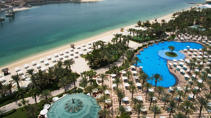 The pool and beach of the Atlantis Hotel is seen with the skyline of the Dubai Marina visible in the distance in Dubai, United Arab Emirates, Tuesday, July 14, 2020. Dubai has reopened for tourists, including at the Atlantis on Dubai's man-made Palm Jumeirah archipelago, though workers there expect a slow growth through the rest of the year amid the ongoing coronavirus pandemic. (AP Photo/Jon Gambrell)