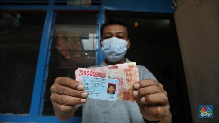 Petugas Pos Indonesia menyalurkankan bantuan sosial (bansos) ke pemukiman di wilayah Kenari, Jakarta Pusat, Rabu (6/1/2021). Pemerintah telah meresmikan penyaluran bantuan tunai se-Indonesia hari ini.  (CNBC Indonesia/Andrean Kristianto)