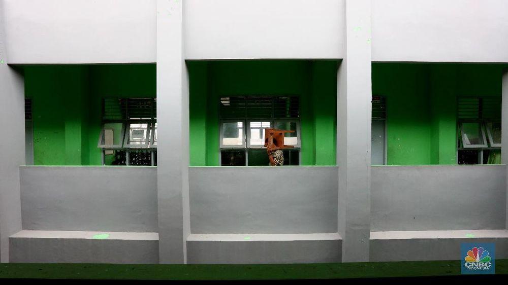 Penjaga sekolah membereskan ruang sekolah yang kosong di Depok, Jawa barat, Rabu (6/1/2021). Kegitan pembelajaran secara tatap muka di wilayah Jawa Barat yang direncanakan dimulai pada awal bulan Januari 2021 ditunda dengan batas waktu yang belum ditentukan akibat masih tingginya kasus Covid-19. (CNBC Indonesia/Tri Susilo).
