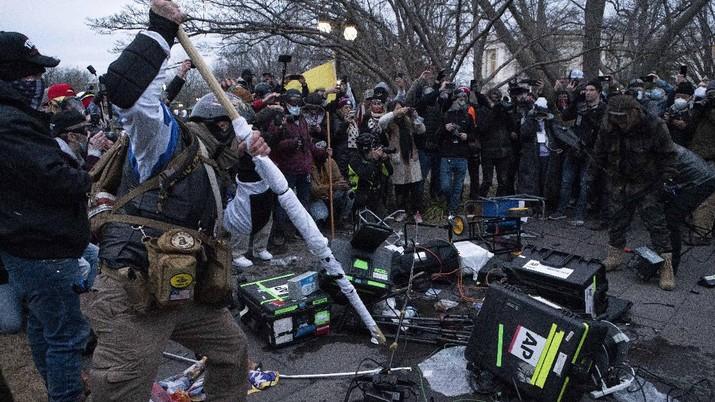 Demonstrators break TV equipment outside the the U.S. Capitol on Wednesday, Jan. 6, 2021, in Washington.  (AP Photo/Jose Luis Magana)