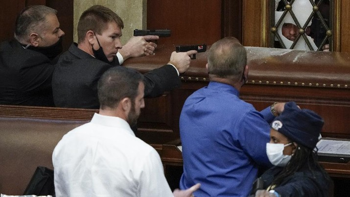 U.S. Capitol Police with guns drawn watch as protesters try to break into the House Chamber at the U.S. Capitol on Wednesday, Jan. 6, 2021, in Washington. (AP Photo/J. Scott Applewhite)